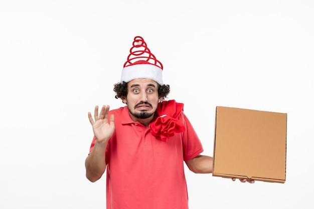 Vista frontal de um jovem segurando uma caixa de comida de entrega na parede branca