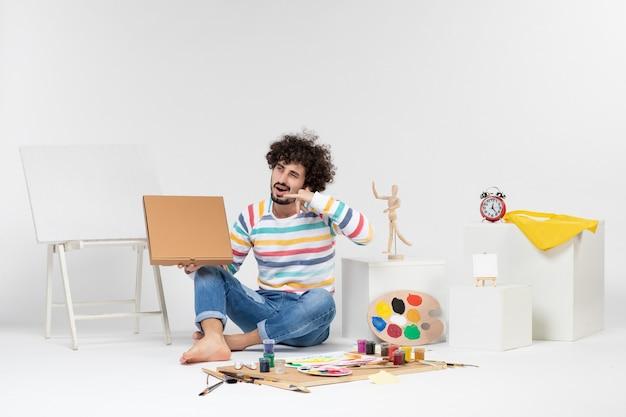 Vista frontal de um jovem segurando uma caixa de pizza na parede branca