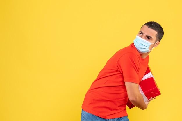 Vista frontal de um jovem segurando uma máscara estéril na parede amarela