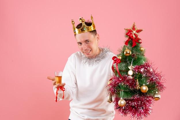 Vista frontal de um jovem segurando uma pequena árvore de natal com uma bebida na parede rosa