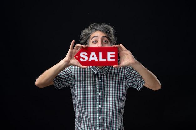 Vista frontal de um jovem segurando uma placa de venda na frente da boca, de pé na parede escura