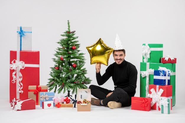Vista frontal de um jovem sentado ao redor de presentes segurando uma estrela dourada na parede branca