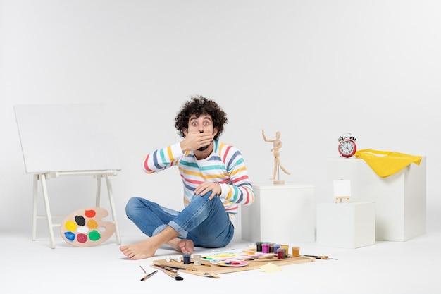 Vista frontal de um jovem sentado ao redor de tintas e desenhos na parede branca