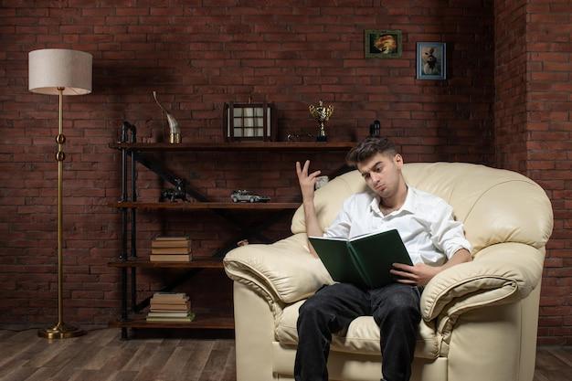 Vista frontal de um jovem sentado no sofá lendo um livro dentro da casa de trabalho à noite, trabalho no quarto