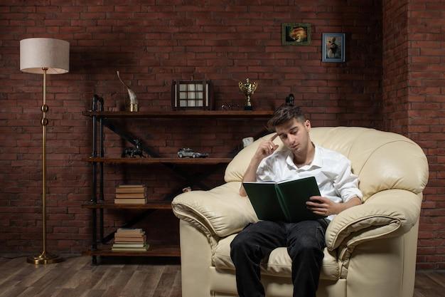 Vista frontal de um jovem sentado no sofá lendo um livro dentro da sala, trabalho, trabalho, noite, casa