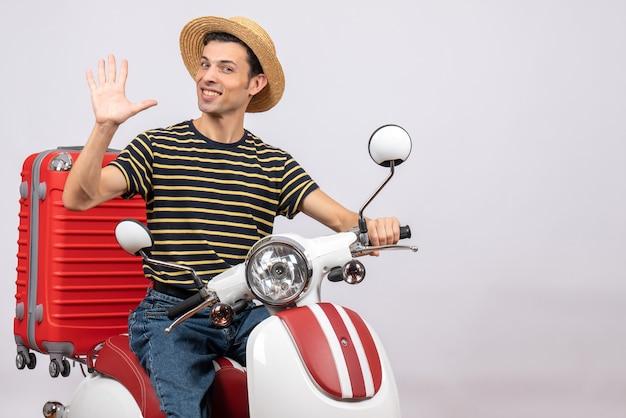 Vista frontal de um jovem sorridente com chapéu de palha na motocicleta acenando com a mão