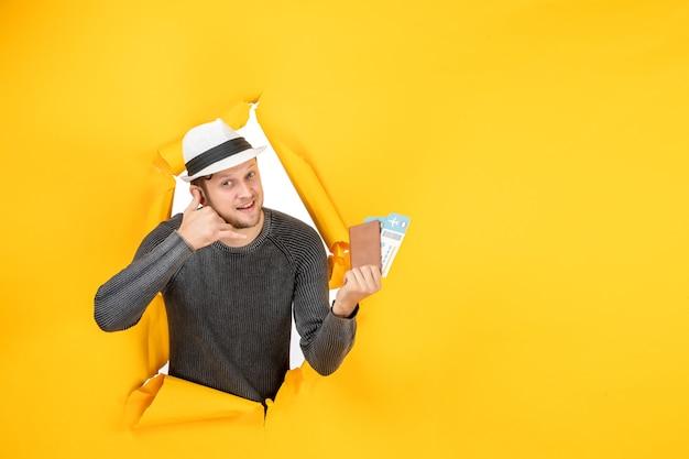 Vista frontal de um jovem sorridente com um chapéu segurando um passaporte estrangeiro com passagem e fazendo o gesto de me ligar em uma parede amarela rasgada
