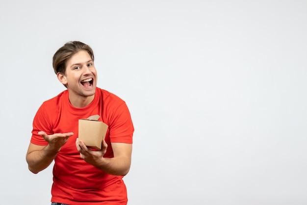 Vista frontal de um jovem sorridente e feliz com uma blusa vermelha apontando uma pequena caixa no fundo branco