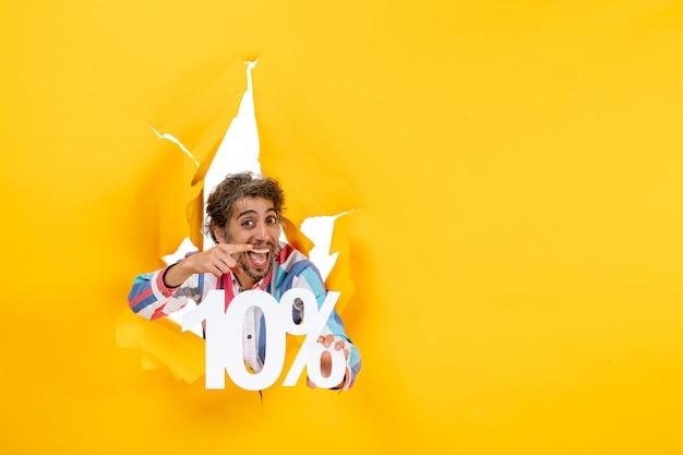 Vista frontal de um jovem sorridente mostrando dez por cento e apontando algo em um buraco rasgado em papel amarelo
