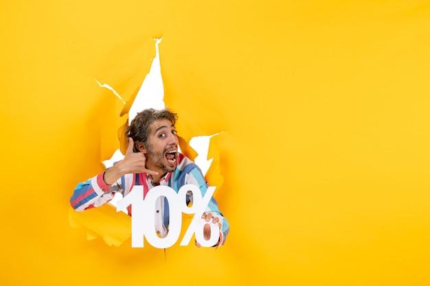 Vista frontal de um jovem sorridente mostrando dez por cento e fazendo o gesto de me ligar em um buraco rasgado em papel amarelo