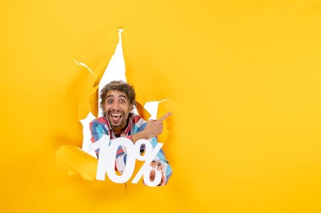 Vista frontal de um jovem sorridente segurando dez por cento apontando para trás em um buraco rasgado em papel amarelo