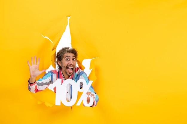 Vista frontal de um jovem sorridente segurando dez por cento e mostrando cinco em um buraco rasgado em papel amarelo