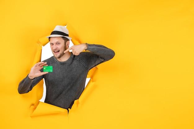 Vista frontal de um jovem sorridente segurando e apontando o cartão do banco em uma parede amarela rasgada