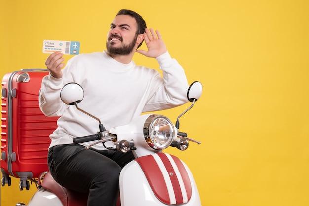 Vista frontal de um jovem sorridente viajando sentado em uma motocicleta com uma mala segurando o ingresso, ouvindo a última fofoca sobre fundo amarelo isolado