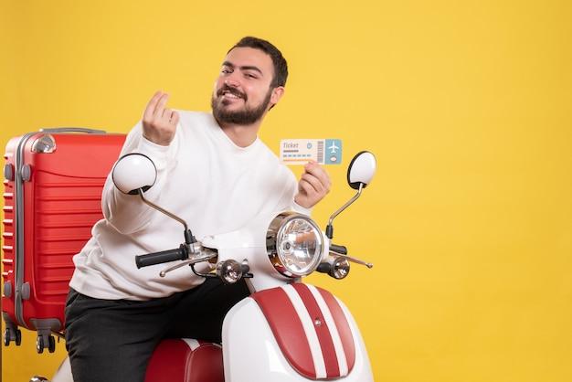 Vista frontal de um jovem sorridente viajando sentado em uma motocicleta com uma mala segurando um bilhete, fazendo gesto de dinheiro em fundo amarelo