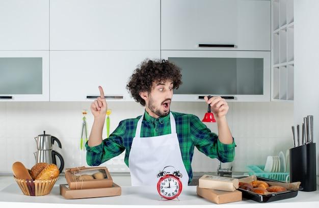 Vista frontal de um jovem surpreso em pé atrás da mesa, vários doces e mostrando a campainha vermelha apontando para cima na cozinha branca