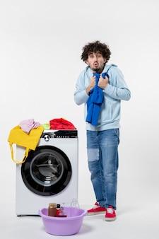 Vista frontal de um jovem tirando roupas limpas da máquina de lavar na parede branca