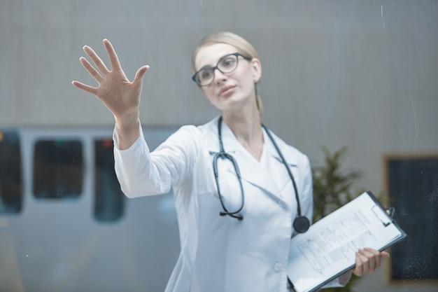 Vista frontal de um jovem trabalhador da área médica com um estetoscópio no pescoço que está desenvolvendo um plano em seu consultório usando uma interface de tela digital tátil. o conceito de altas tecnologias