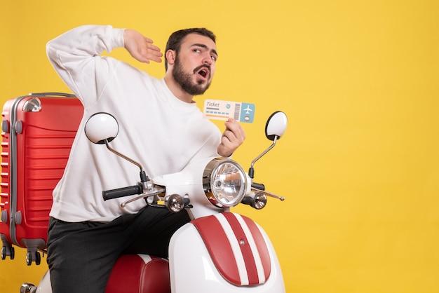 Vista frontal de um jovem viajando sentado em uma motocicleta com uma mala segurando o ingresso, ouvindo a última fofoca sobre fundo amarelo isolado