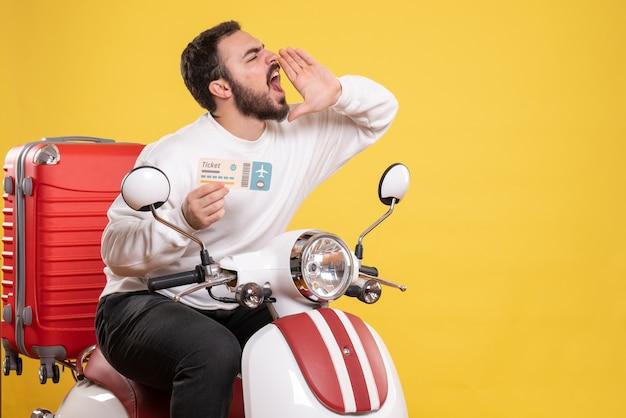 Vista frontal de um jovem viajando sentado em uma motocicleta com uma mala segurando um bilhete chamando alguém em fundo amarelo isolado