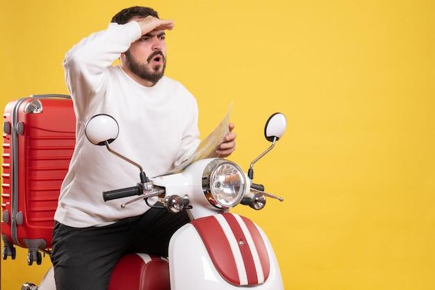 Vista frontal de um jovem viajando sentado em uma motocicleta com uma mala segurando um mapa em fundo amarelo isolado