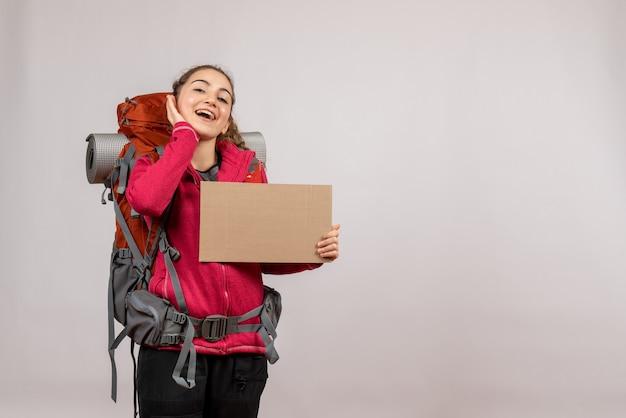 Vista frontal de um jovem viajante alegre com uma grande mochila segurando um papelão na parede cinza