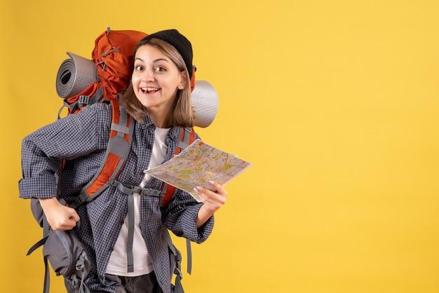 Vista frontal de um jovem viajante alegre com uma mochila segurando o mapa