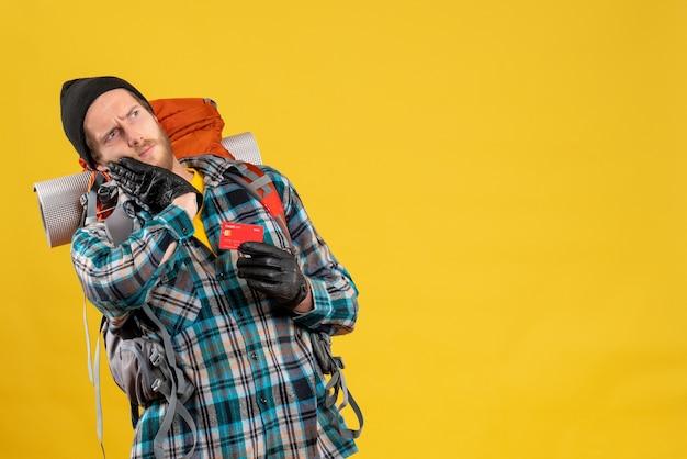 Vista frontal de um jovem viajante barbudo com um mochileiro segurando um cartão de descontos
