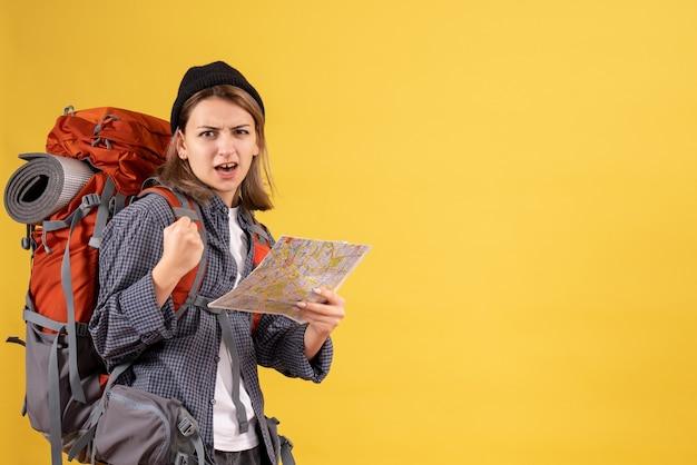 Vista frontal de um jovem viajante confuso com uma mochila segurando o mapa