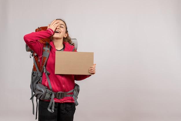 Vista frontal de um jovem viajante feliz com uma grande mochila segurando um papelão na parede cinza