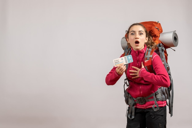 Vista frontal de um jovem viajante perplexo com uma grande mochila segurando a passagem na parede cinza