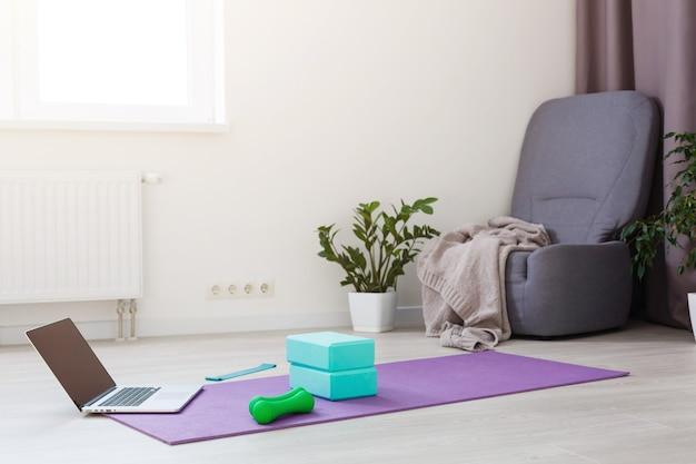 Vista frontal de um laptop com tela de cópia em branco, ioga em casa