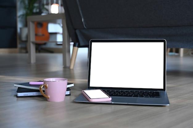 Vista frontal de um laptop em branco, telefone celular, xícara de café e notebook no piso de madeira da sala de estar.