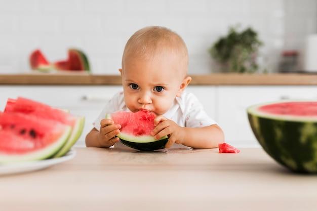 Vista frontal de um lindo bebê comendo melancia