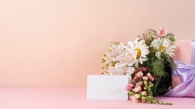 Vista frontal de um lindo buquê de flores com cartão em branco