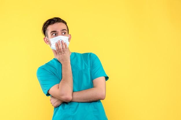 Vista frontal de um médico com cara de surpresa na parede amarela