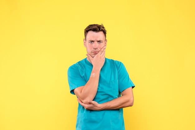 Vista frontal de um médico com expressão estressada na parede amarela