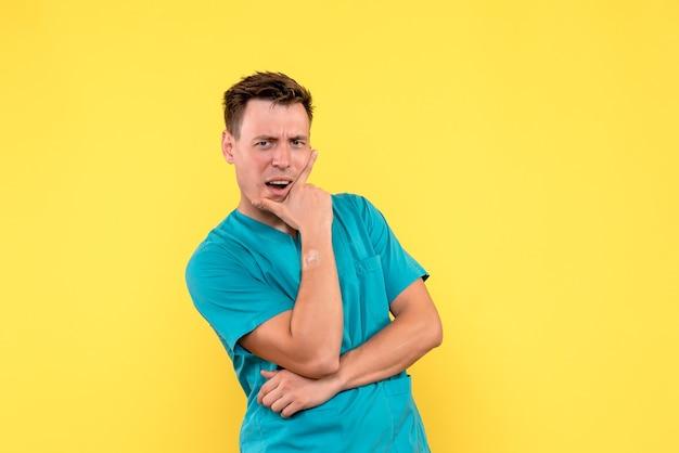 Vista frontal de um médico com expressão pensativa na parede amarela