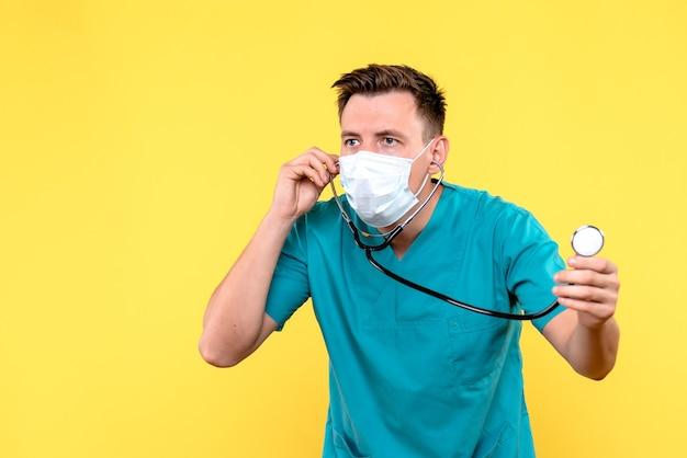 Vista frontal de um médico com máscara e tonômetro na parede amarela