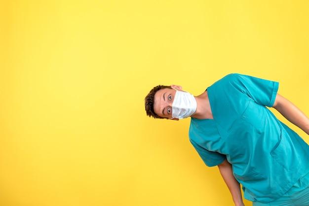 Vista frontal de um médico com máscara estéril na parede amarela