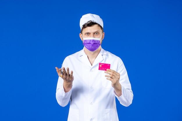 Vista frontal de um médico em terno médico e máscara roxa segurando injeção e cartão de crédito em azul