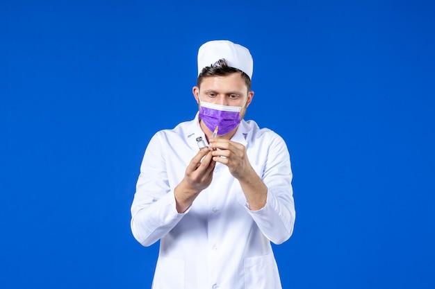 Vista frontal de um médico em traje médico e máscara com injeção e vacina em azul