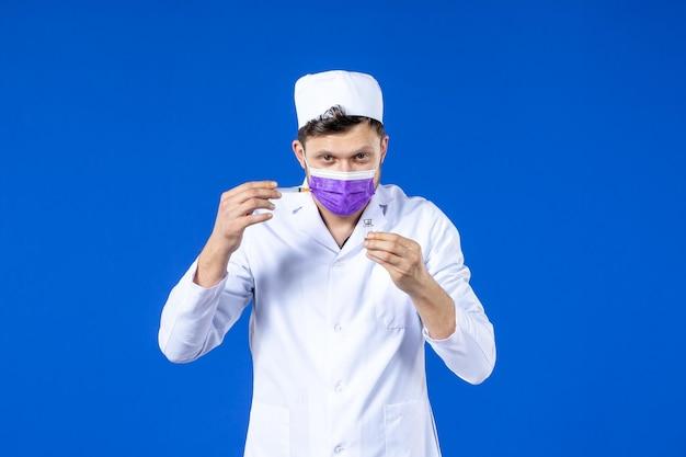 Vista frontal de um médico em traje médico e máscara segurando vacina e injeção em azul