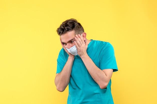 Vista frontal de um médico estressado na máscara na parede amarela