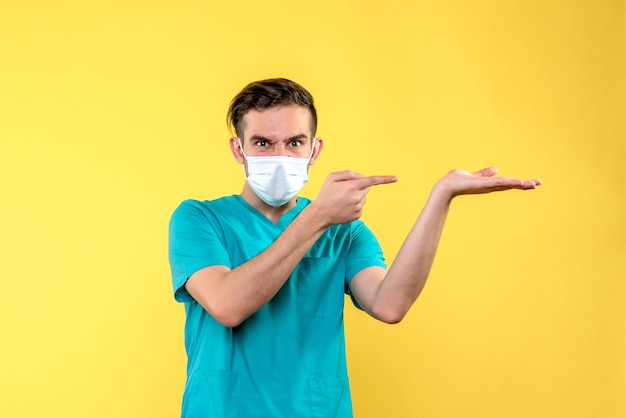 Vista frontal de um médico na parede amarela