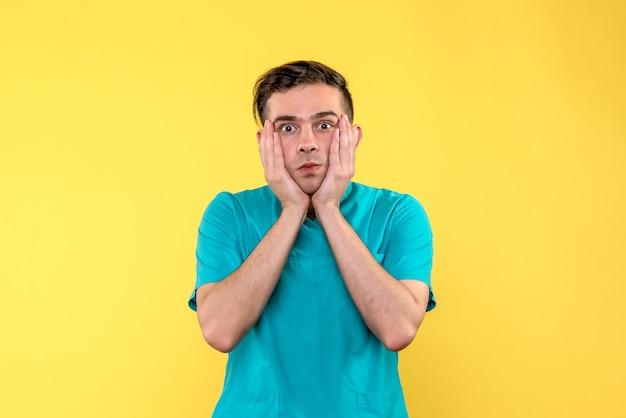 Vista frontal de um médico olhando com atenção na parede amarela