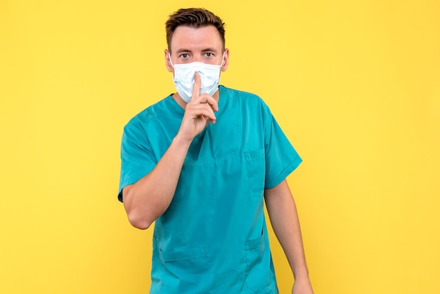 Vista frontal de um médico pedindo para ficar quieto na parede amarela