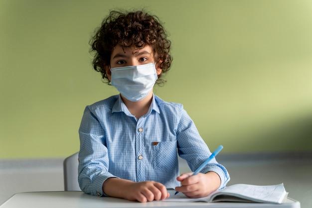 Vista frontal de um menino com máscara médica na escola durante a pandemia