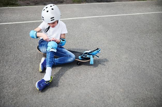 Vista frontal de um menino esportivo com capacete de segurança sentado no skate no asfalto do parquinho e colocando joelheiras de proteção