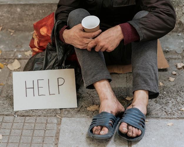 Vista frontal de um morador de rua ao ar livre com sinal de ajuda e copo